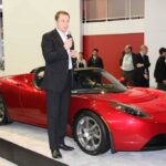 Tesla CEO Elon Musk, shown with the original battery-powered Roadster.