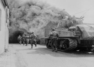 Soldiers of the 55th Armored Infantry Battalion and tank of the 22nd Tank Battalion, move through smoke filled street.