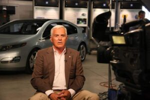 GM Vice Chairman Bob Lutz sits in front of the Chevy Volt, which got a 230 mpg rating under a new government mileage standard.