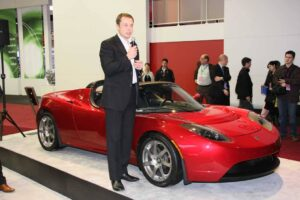 Tesla Motors founder Elon Musk, shown here .with the Tesla Roadster, at the Detroit Auto Show, January 2009