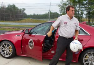 General Motors President North America Mark Reuss gets out of the Cadillac CTSv after taking the vehicle on hot laps around the track at the Monticello Motor Club.