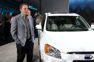 Tesla CEO Elon Musk shown with the Toyota RAV4-EV that uses his company's powertrain.