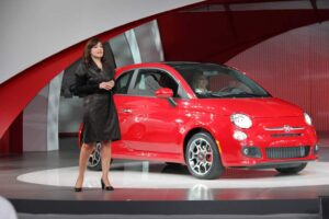 Laura Soave, head of the Fiat brand in North America, stands with the new 500 minicar.