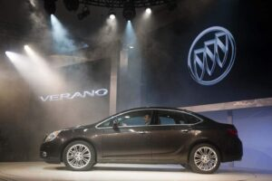 The 2012 Buick Verano rolls onto the stage during its Detroit Auto Show unveiling.