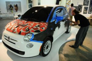 Artists working on a custom Fiat 500 paint job.
