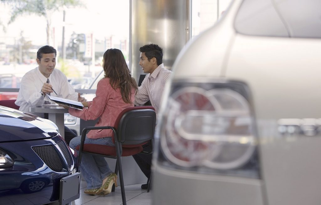 Salesman and couple sitting at desk in car showroom, focus on background