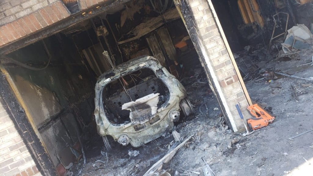 charred Chevy Bolt in garage