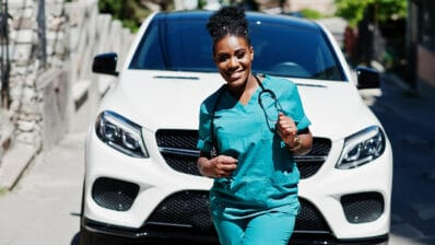 African american doctor female at lab coat with stethoscope posed outdoor against white suv car.