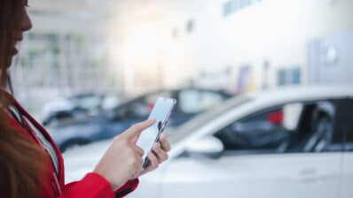 A female is using a phone in the car showroom.