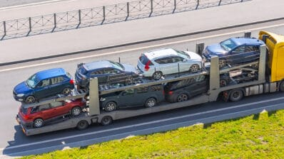 Transportation of new cars on a trailer with a truck for delivery to dealers